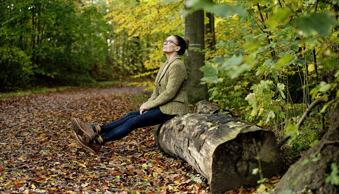 Una mujer sentada en un árbol caído