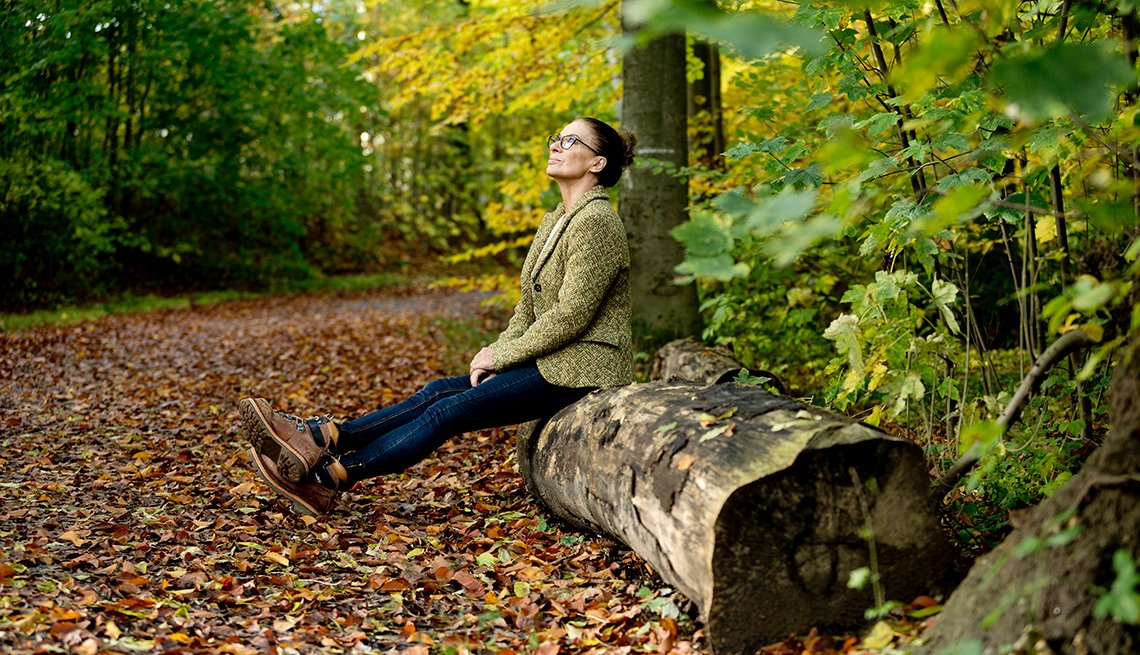 woman sitting on a tree trunk in the wood looking relaxed