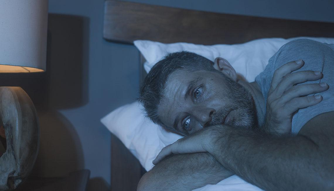 Un hombre en su cama despierto y triste