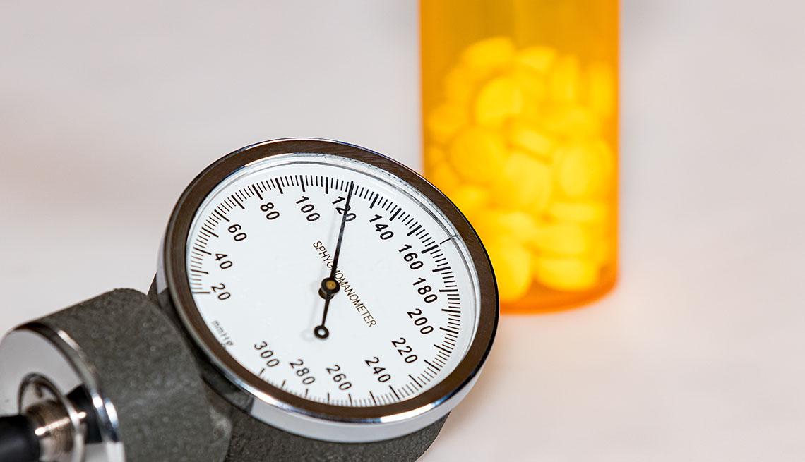 sphygmomanometer dial and bottle of pills
