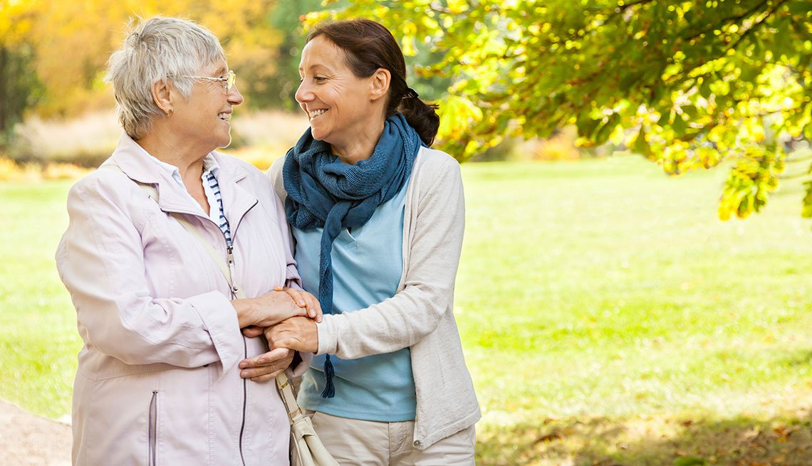 senior woman and carer walking in the park