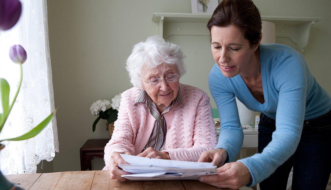 Cómo manejar tu tiempo efectivamente si cuidas de alguien - Mujer le enseña documentos a una abuela