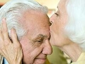 Pareja de adultos mayores, mujer besa la frente del hombre