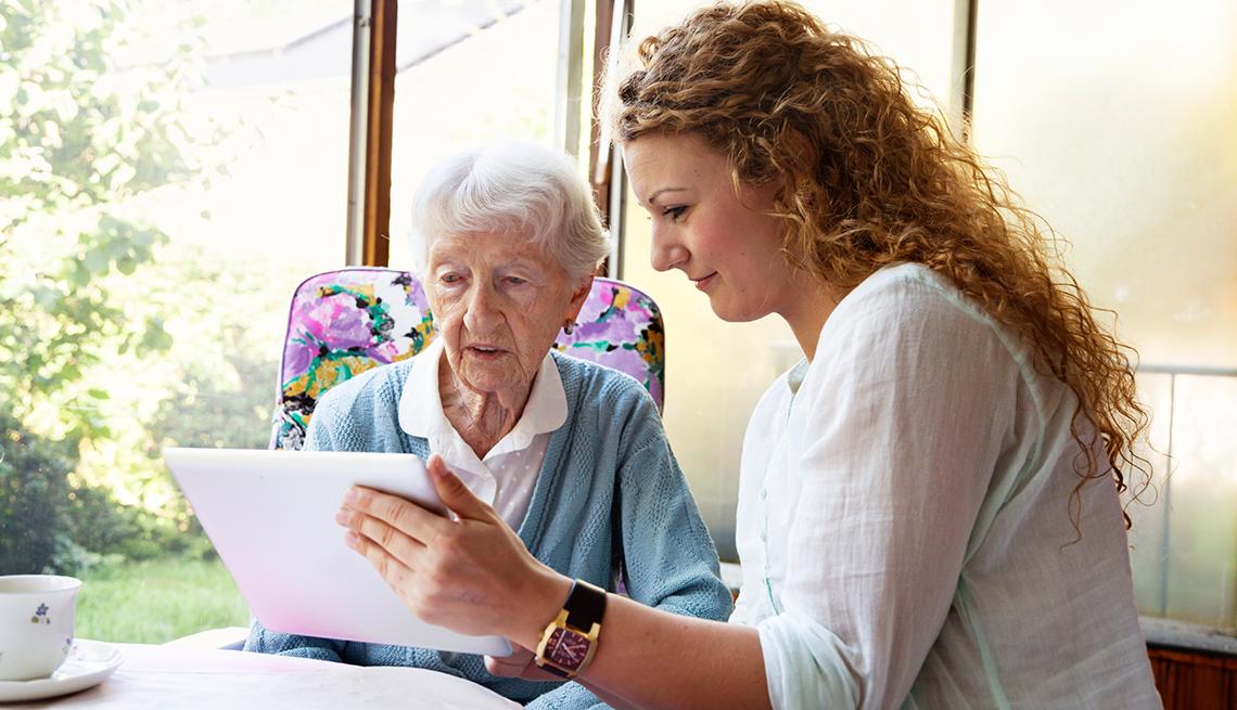 Una mujer mostrando una tableta a su abuela.
