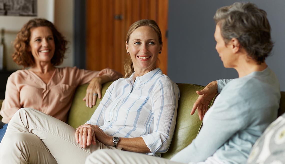 Tres mujeres sentadas en un sofá hablando durante un grupo de apoyo para cuidadores.