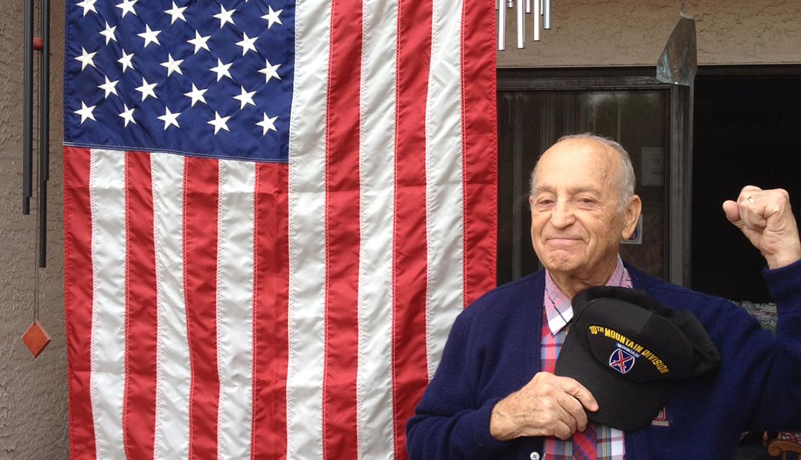 Robert Goyer, veterano de la Segund Guerra Mundial parado frente a una bandera de Estados Unidos
