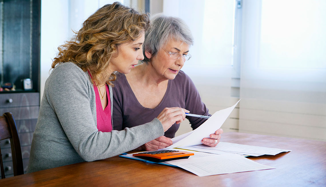 Senior woman with her carer calculating bills