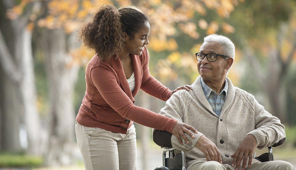 Hija afroamericana llevando a su  abuelo en silla de ruedas