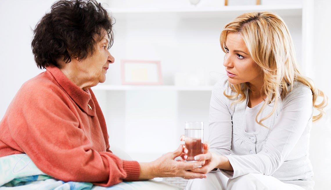 Mujer adulta recibe un vaso con agua de otra mujer que la está cuidando