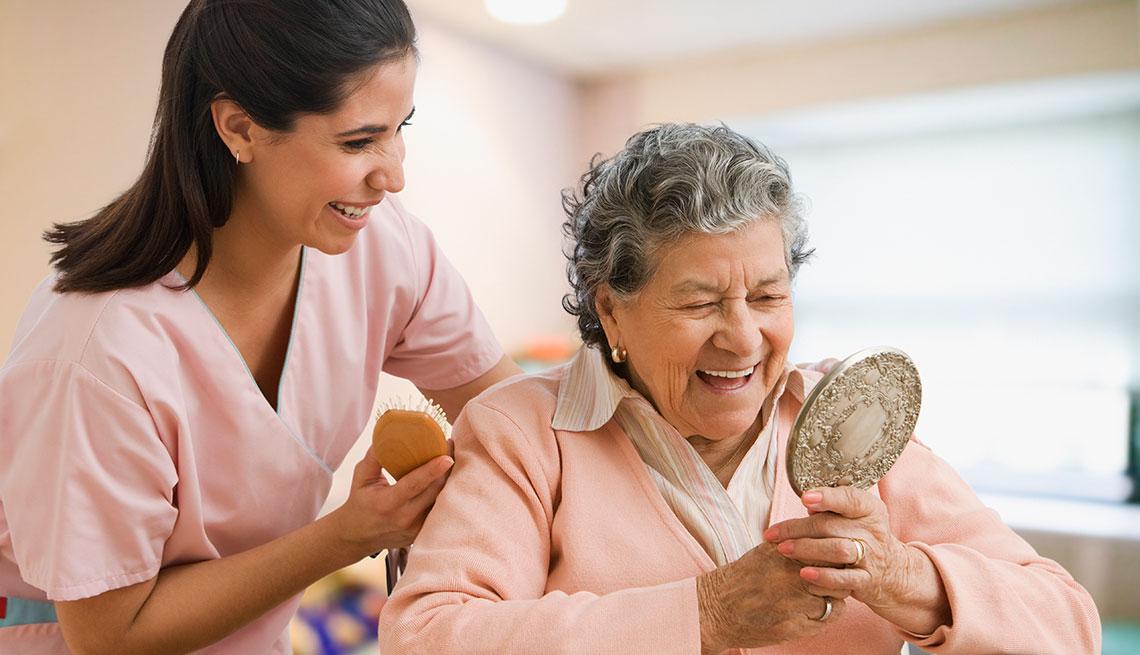 nurse helping senior woman with hair