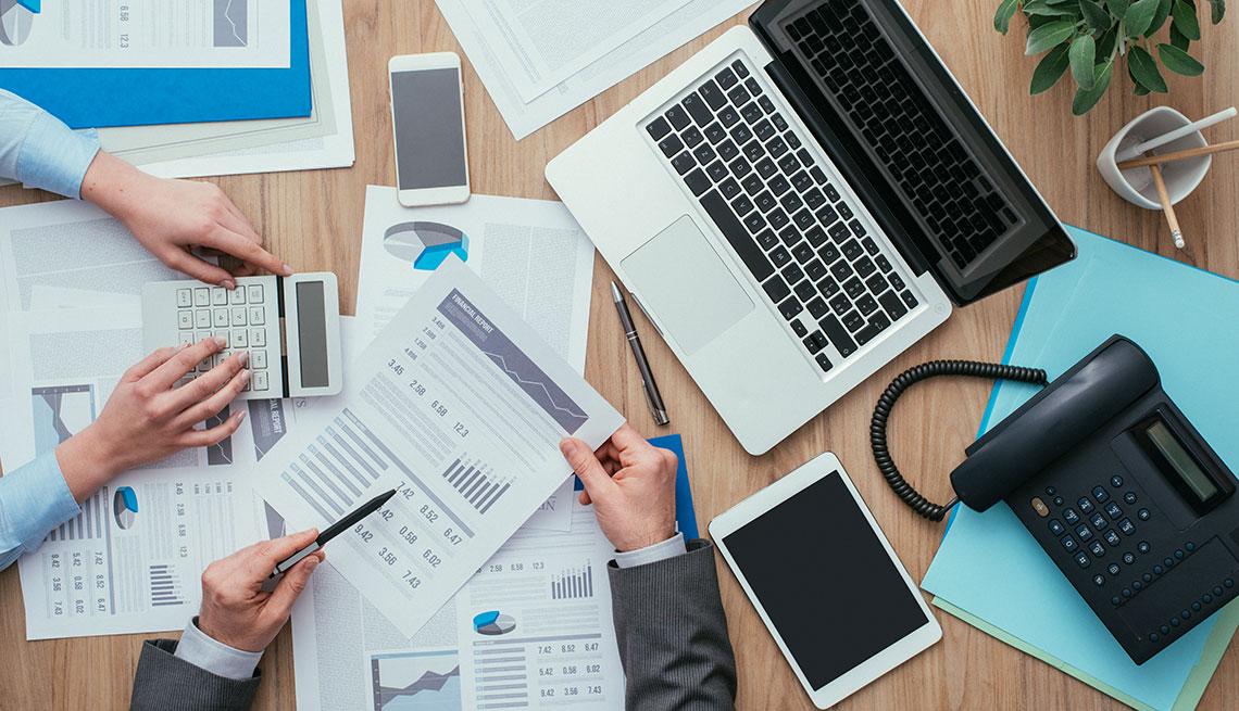 Escritorio lleno de documentos financieros y aparatos digitales