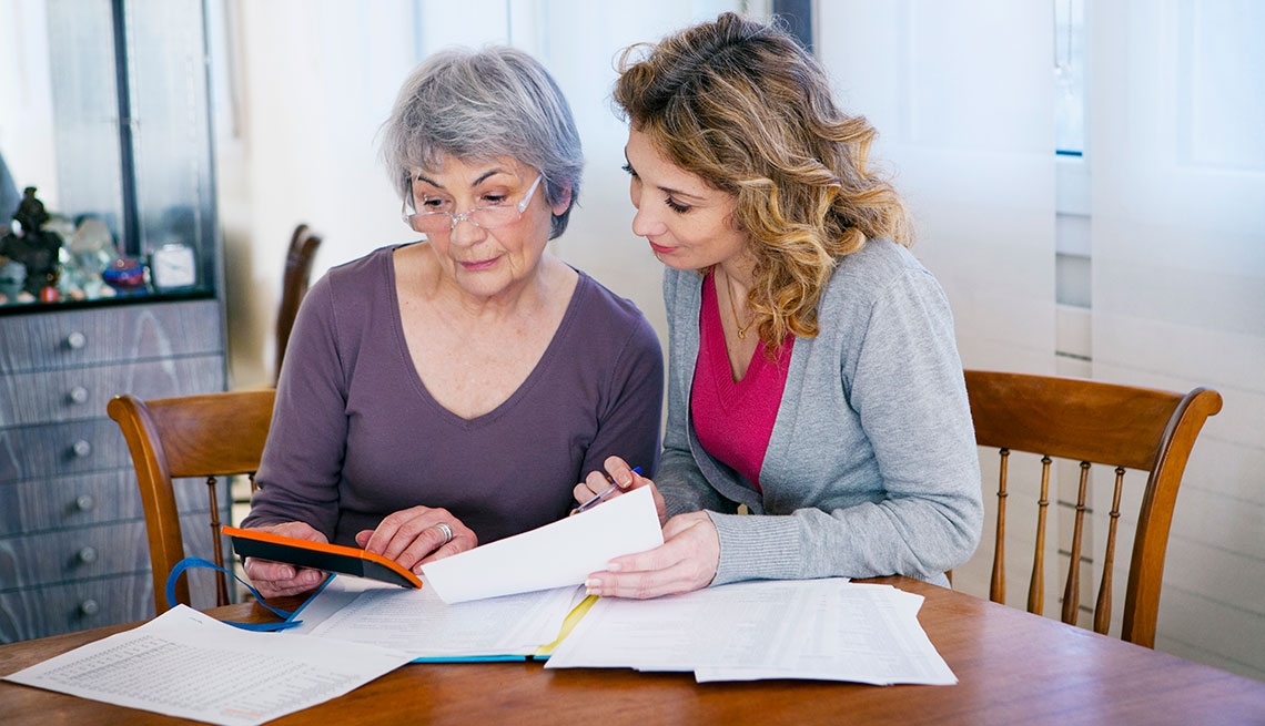 A daughter helping her elderly mother organize her financial records and legal documents