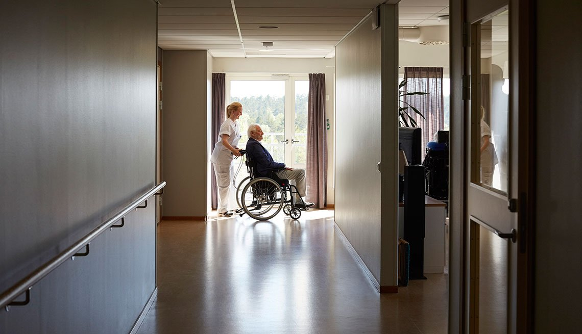 nurse pushing an older man on a wheel chair at a nursing home