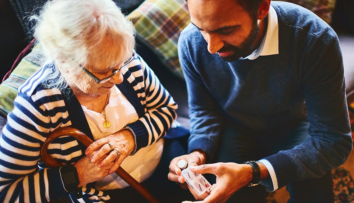 Man explaining medicine dosage to senior female woman.