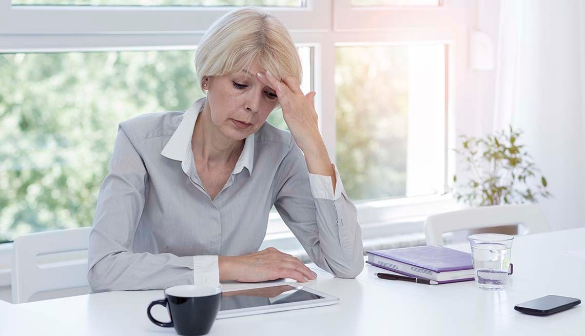 Mature businesswoman with hand on her head sitting at a desk, looking stressed.