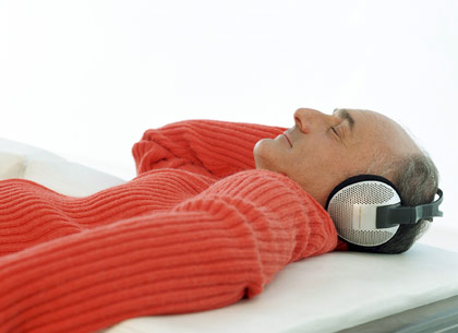 man in prone position with ear phones