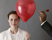 A woman with a red balloon and a man's arm holding a dart poised to burst the balloon.