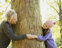 Grandmother and granddaughter (8-9) playing around tree