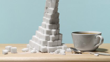 Una taza de café y una montaña de cubos de azúcar