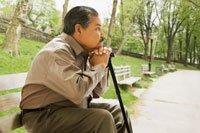 Hombre hispano sentado en la banca de un parque apoyándose en un bastón - Unos 300.000 estadounidenses mayores de 65 años se fracturan la cadera cada año.