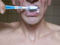 Hombre cepillándose los dientes. La limpieza dental puede reducir el riesgo de enfermedades cardiacas y ataques al corazón.