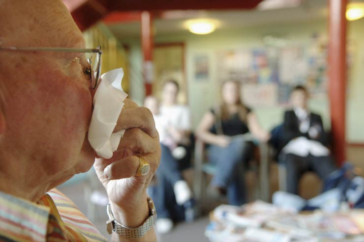 Elderly man sneezing in a crowded doctor's waiting room