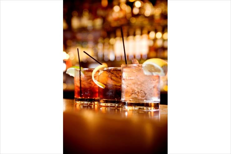 Mixed drinks along a bar with lemon wedges