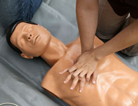 Woman learns cardiopulmonary resuscitation CPR on mannequin