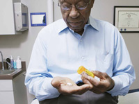 African American mature male sitting on an examination bed in a doctor's office, looking at prescription pills.