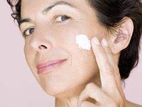 Mujer aplicándose crema en la mejilla. Cuales de los productos funcionan mejor para el cuidado de su piel?