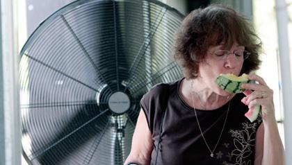 Mujer mayor comiendo una sandia con un ventilador en su espalda - Cómo protegerse del calor