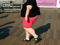 An obese woman walks on a boardwalk-Many boomers are obese