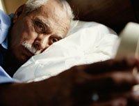 hombre afectado por la apnea del sueño revisando su alarma