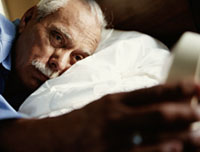 man affected by sleep apnea checking his alarm clock