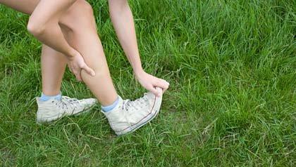 Los calambres en las piernas, cómo aliviarlos - Mujer se estira la pierna.