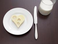 Lácteos bajos en grasa pueden evitar un derrame cerebral - Sándwich de queso cortado en forma de corazón y vaso de leche.