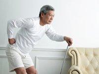 5 consejos para una cirugía de reemplazo de cadera con éxito - Hombre mayor sosteniendo su cadera por un bastón.