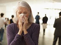 Flu facts- a senior woman blowing her nose