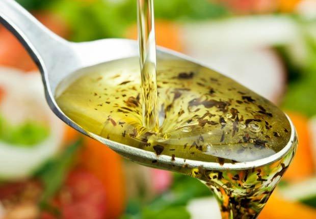 Cucharada de aceite de oliva con ensalada en el fondo - 10 Beneficios del aceite de oliva