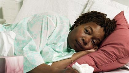 Sick African American woman lying on couch, Bad flu season CDC