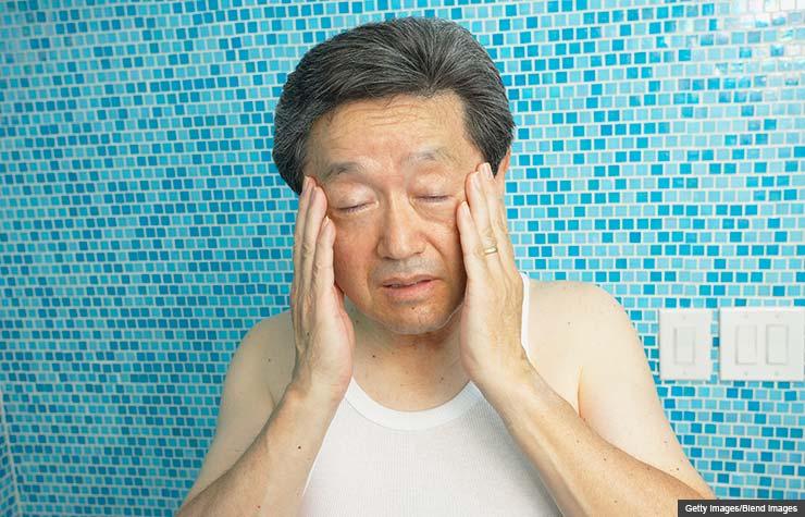 Asian man rubbing his temples in bathroom, Symptoms