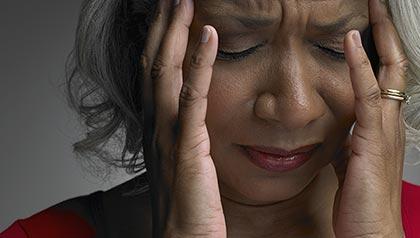Mujer madura con la cabeza en las manos y los ojos cerrados con sintoma de un dolor de cabeza