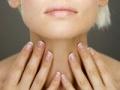 Mujer se toca el cuello - ¿Cuánto sabe usted acerca de la tiroides?
