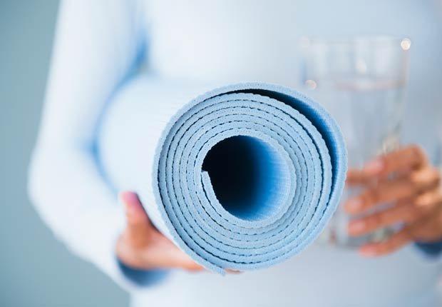Mujer sosteniendo un colchón para hacer yoga - Combatir la depresion sin medicamentos