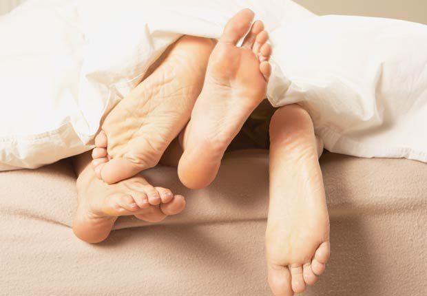 Pies descalzos de una pareja debajo de las cobijas - Combatir la depresion sin medicamentos