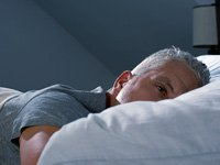 Man lying awake in bed with insomnia, Prescription sleeping pills not first choice for insomnia
