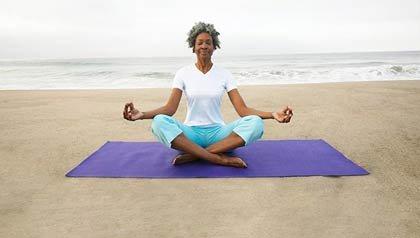 Mujer haciendo yoga en la playa - El yoga puede ayudar a aliviar los síntomas de dolores crónicos