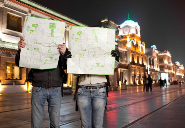 Tourists holding maps