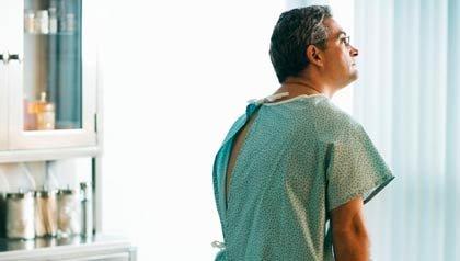 Hombre sentado con una bata de hospital en un consultorio médico - Tengo que hacerme una colonoscopia - Cancer colon