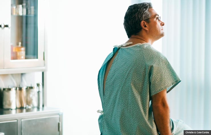 Man sitting on examination table in hospital gown, Potentially unnecessary colonoscopies